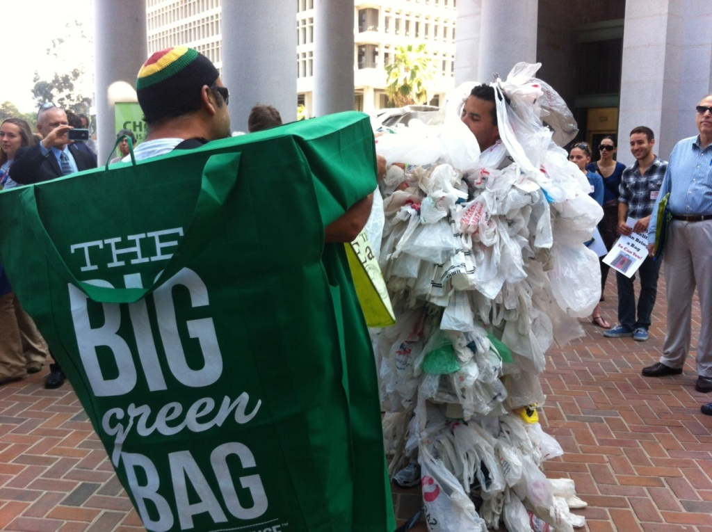 Activists Mauricio Reza (L) and James Alamillo (R) perform a staged fight over a bag ban minutes before the Los Angeles City Council considers moving a prohibition forward. Forty-five jurisdictions in California have banned single use sacks.