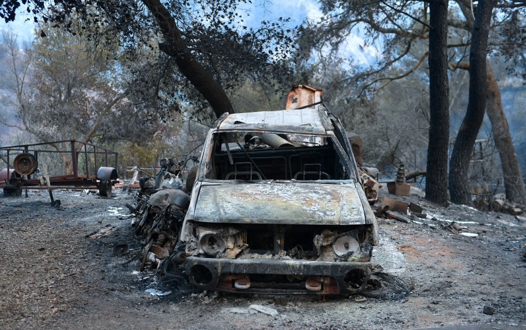 The remains of damaged vehicles remain outside a home in the hills of Toro Canyon north of Santa Barbara, California on December 12, 2017 as firefighters continue to battle the Thomas Fire.