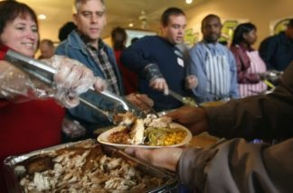Volunteers dish out Thanksgiving dinner to the needy during a free banquet prepared at Smokey Jackson's Boneyard grill in Aurora, Colorado. Homeless and disadvantaged people were transported to the event by Christian aid groups, whose members helped serve the meal.