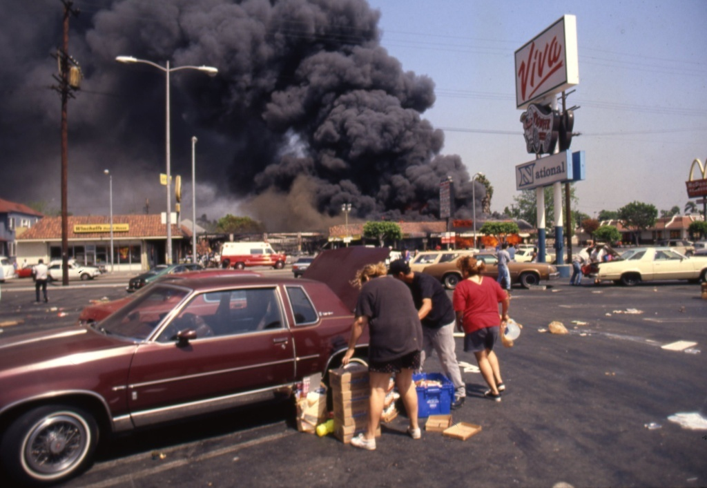 Looters load up a car at the Viva shopping center near a billowing fire during the rioting that erupted in Los Angeles on April 29, 1992, after a jury found four Los Angeles Police Department officers not guilty in the beating of Rodney King.