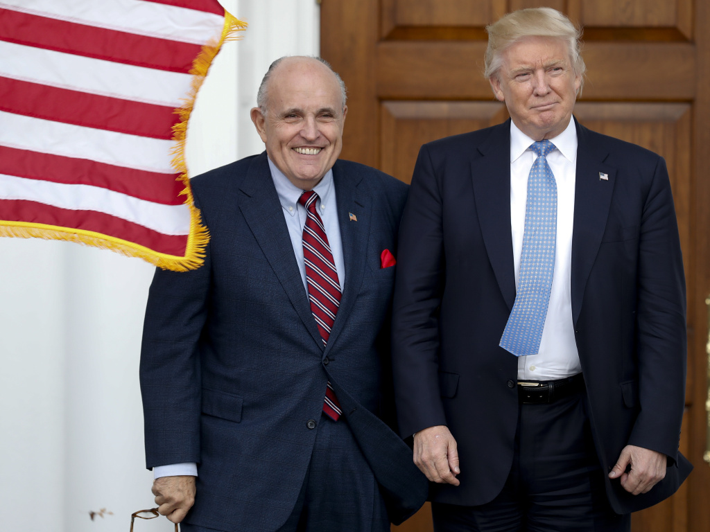 Rudy Giuliani is seen here with Donald Trump shortly after Trump's election victory in 2016. Federal authorities raided Giuliani's apartment Wednesday, the former New York City mayor's attorney said.