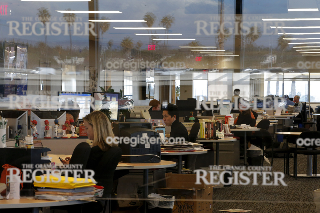 In this Dec. 27, 2012, file photo, arts writer Richard Chang, center, works on his computer in the newsroom of the Orange County Register in Santa Ana, California. Freedom Communications Inc., owner of the Orange County Register, has filed for Chapter 11 bankruptcy protection.