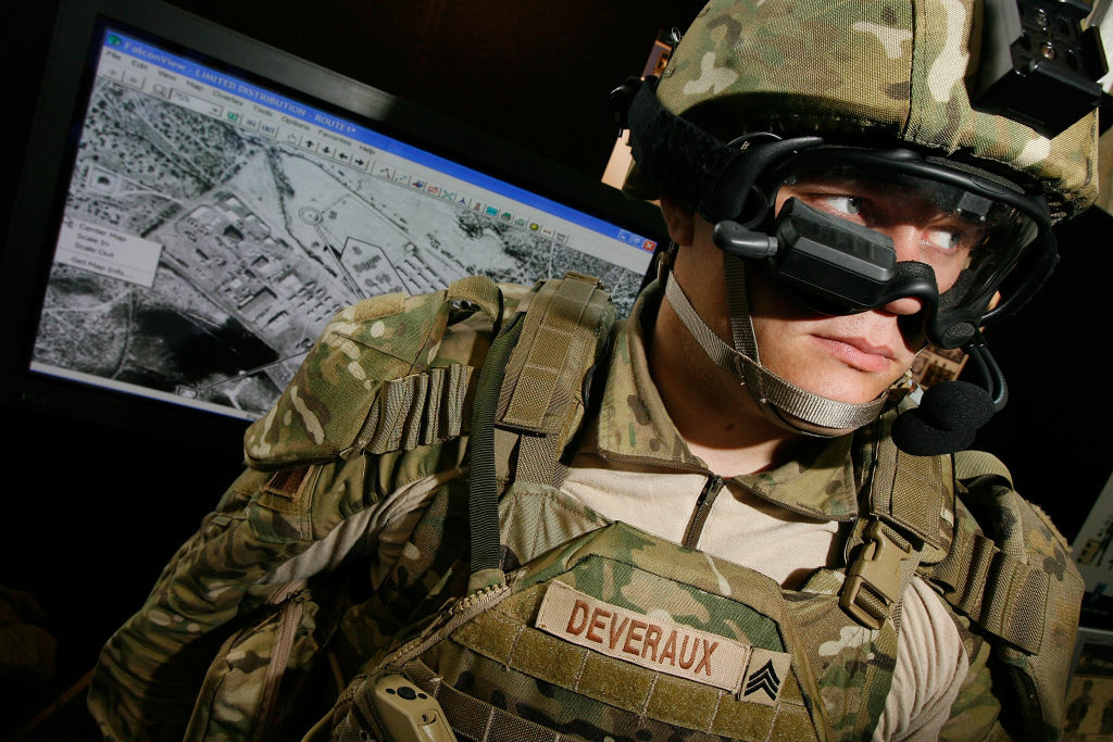 US Army Sgt. Josh Deveraux models the goggle-mounted display (GMD) below his right eye, which can be used to look at the battlefield, part of his Future Force Warrior high-tech combat outfit, during the US Army Soldier Modernization Day expo in the Rayburn House Office Building June 6, 2007 in Washington, DC. The Future Force Warrior integrates GPS, advanced communications, body armor and other computer systems to help coordinate ground troops, aircraft and vehicles in the field. The expo displayed weapons, clothing, body armor and combat rations that are on the cutting edge of military technology.