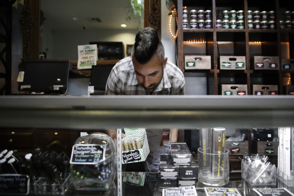 In this June 27, 2017, photo, Jerred Kiloh, owner of the Higher Path medical marijuana dispensary, stocks shelves with with cannabis products in Los Angeles. On a typical day, $15,000 can change hands in his dispensary, where a steady stream of customers pick from shelves stocked with hundreds products, from cannabis-infused lip balm to potent concentrates that look like thin sheets of amber-colored ice.