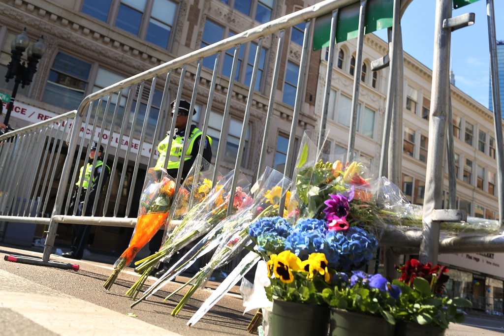 BOSTON, MA - APRIL 16:  Flowers are left at a security gate near the scene of yesterday's bombing attack at the Boston Marathon on April 16, 2013 in Boston, Massachusetts. The twin bombings, which occurred near the marathon finish line, resulted in the deaths of three people while hospitalizing at least 128. The bombings at the 116-year-old Boston race, resulted in heightened security across the nation with cancellations of many professional sporting events as authorities search for a motive to the violence.  (Photo by Spencer Platt/Getty Images)
