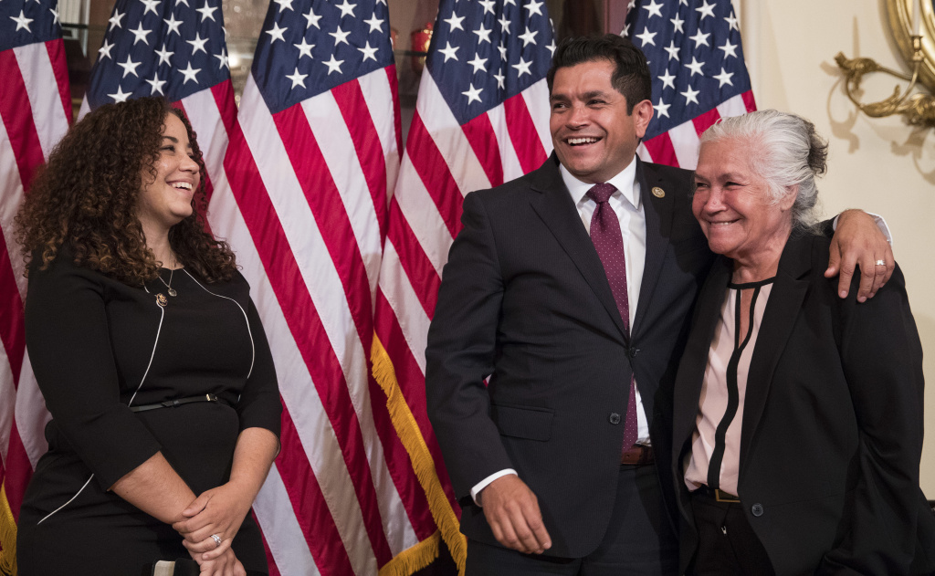 Jimmy Gomez, Democrat from Los Angeles, puts his arm around his mother, Socorro Gomez, right, as his wife, Mary Hodge, looks on before participating in a ceremonial swearing-in on Capitol Hill in Washington, Tuesday, July 11, 2017.