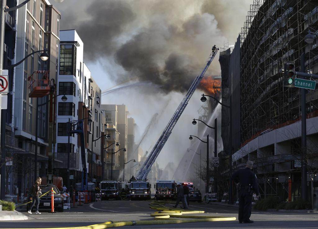 Firefighters battle a fire burning in San Francisco, Tuesday, March 11, 2014. The major fire burning in San Francisco's Mission Bay neighborhood sent an enormous plume of black smoke high into the sky. There were no initial reports of injuries. The four-alarm fire that began about 5 p.m. was ravaging a high-rise building under construction and moving down a block.