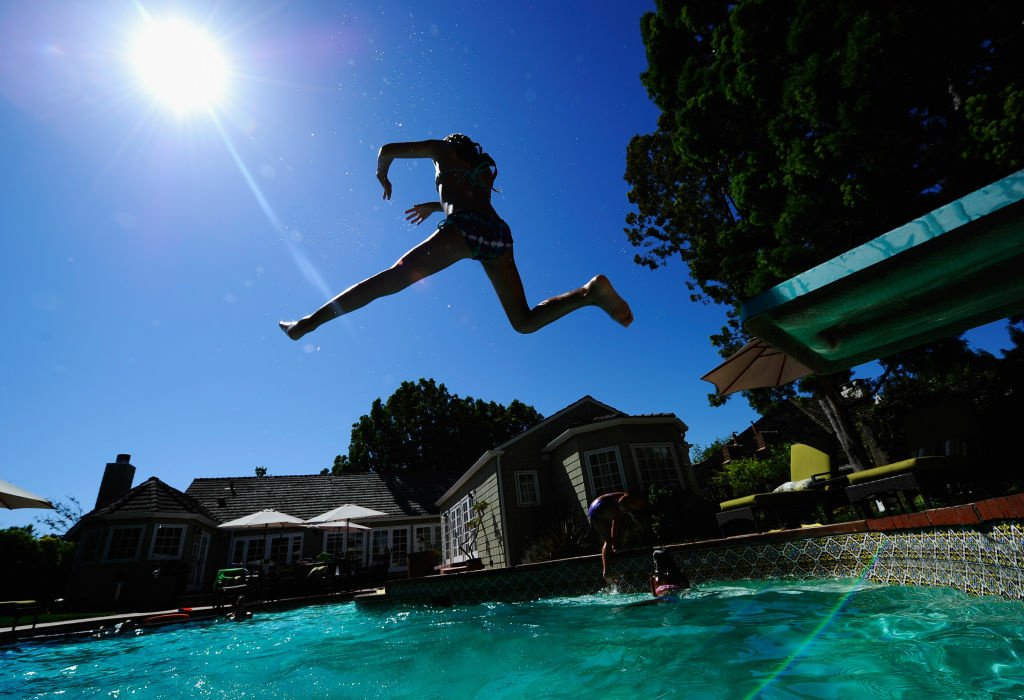 Helena Econn, 7, jumps off the diving board as she plays in a backyard pool during a 2010 L.A. heat wave.