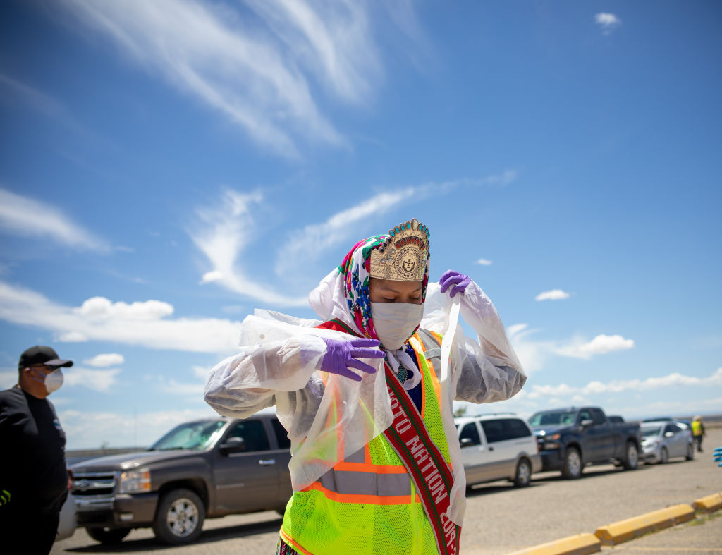 Miss Navajo Nation Shaandiin P. Parrish puts on a white gown to help distribute food, water, and other supplies to Navajo families on May 27, 2020 in Huerfano on the Navajo Nation Reservation, New Mexico.