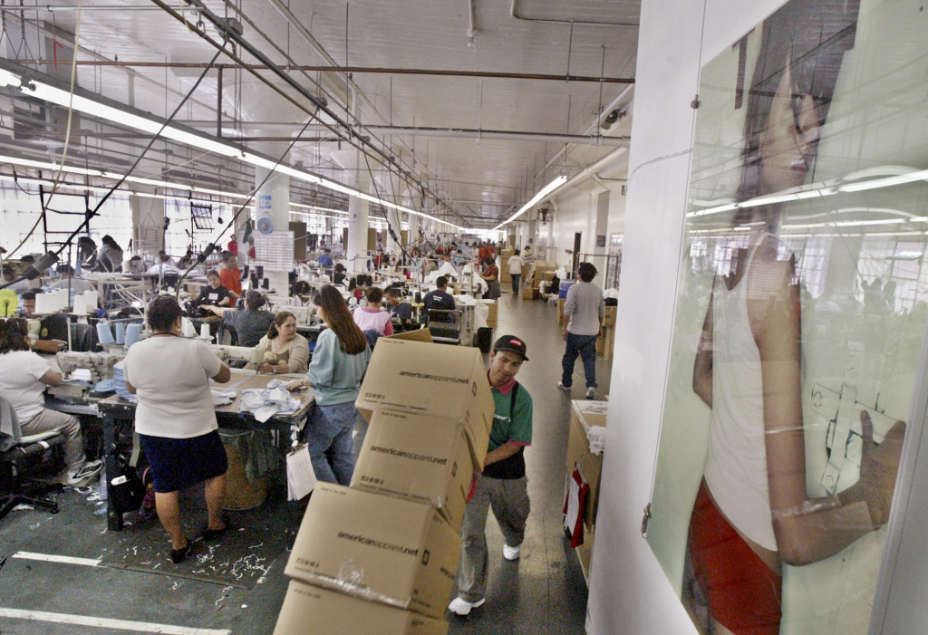 A worker moves several boxes of American Apparel garments on the sewing floor in Los Angeles in this 2004 file photo.