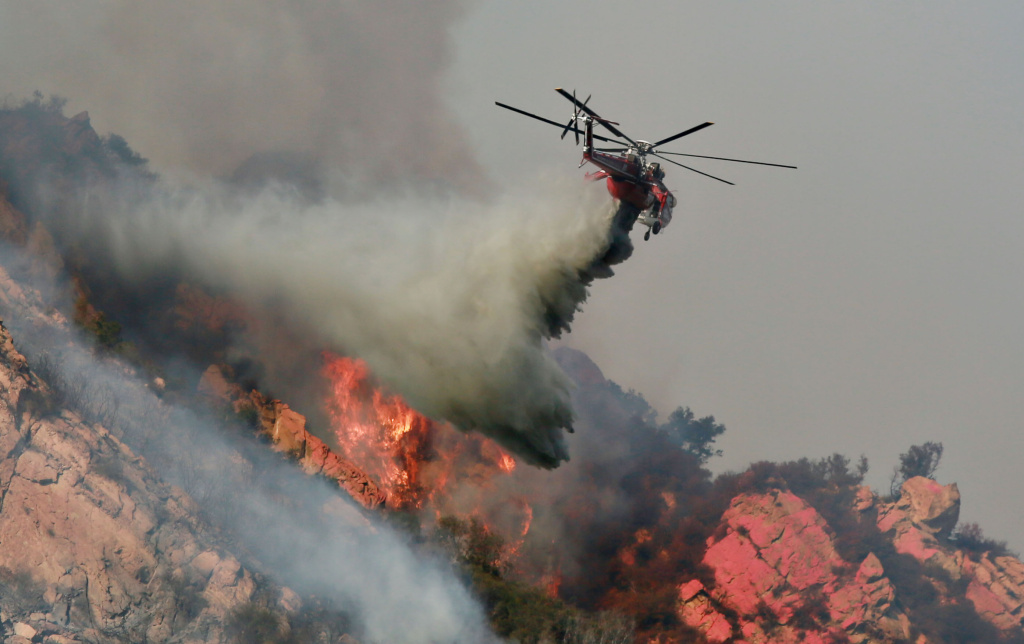 A helicopter drops flame retardant on a wildfire on November 10, 2018 in Malibu, California. The Woolsey fire has burned over 70,000 acres and has reached the Pacific Coast at Malibu as it continues grow.