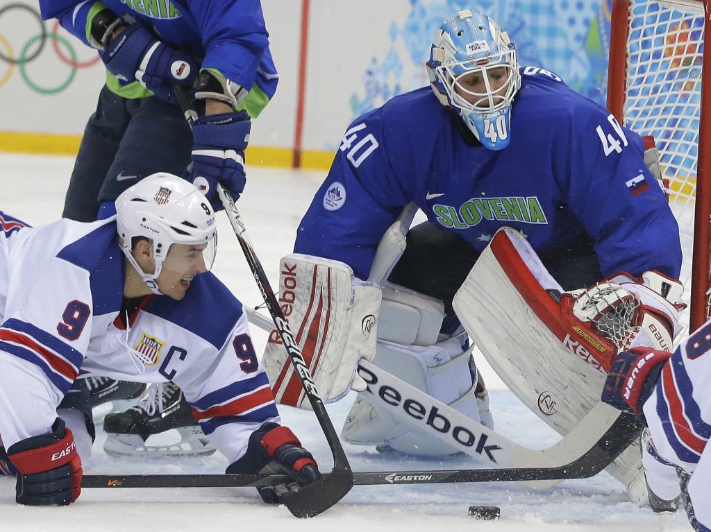 USA forward Zach Parise reaches for a loose puck in front of Slovenia goaltender Luka Gracnar during the 2014 Winter Olympics men's ice hockey game on Sunday.