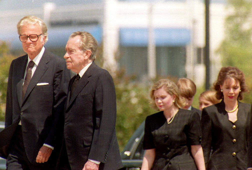 Former President Richard Nixon (2nd-L) is accompanied by evangelist Billy Graham (L) as they arrive at the Richard Nixon Library 25 June 1993 where former First Lady Pat Nixon lay in state.