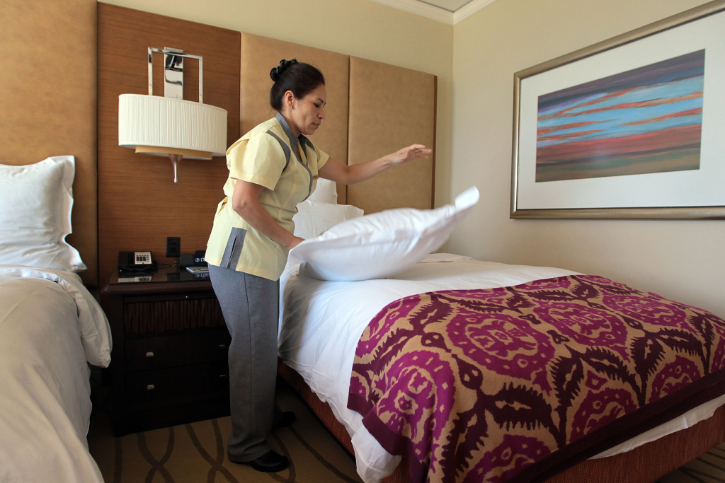 A housekeeper, at the Ritz-Carlton, Key Biscayne hotel prepares a room for a new occupant in Key Biscayne, Florida. Restaurants and hotels are posting new job openings faster than they can fill them.