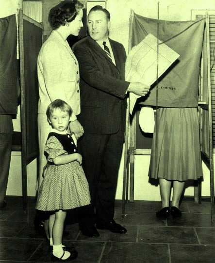 Congressman Patrick J. Hillings and his wife, Phyllis, accompanied by their daughter, Jennifer Ann, cast their votes at their neighborhood polling place in Arcadia on November 4, 1958. He is a Republican candidate for Attorney General.