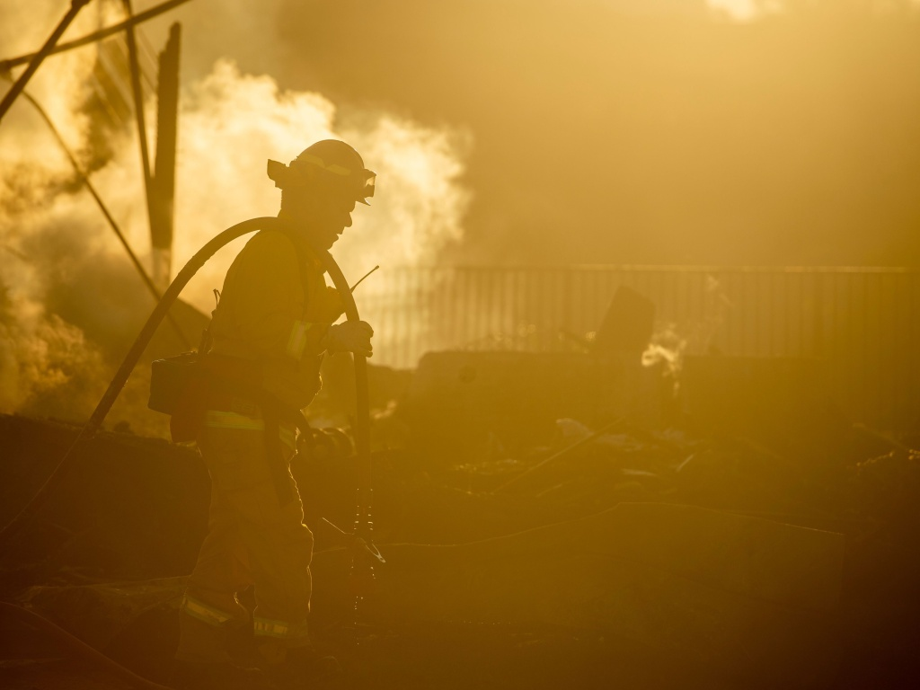 A firefighter sprays down the smoldering remains of a burning home during the Hillside Fire in the North Park neighborhood of San Bernardino, Calif., on Oct. 31, 2019. Some wildland firefighters worry whether they can do their jobs safely during a global pandemic.