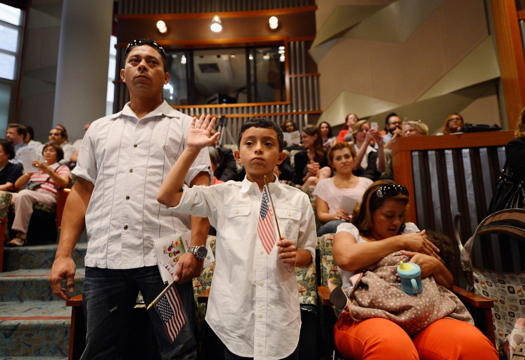 U.S. citizenship candidate Ricardo Barrera, 8, takes the oath of citizenship as his father Ricardo Barrera (L) mother Reina Barrera and his sister Ashley, 1, look on during a naturalization ceremony at the Los Angeles Central Library on September 19, 2012.