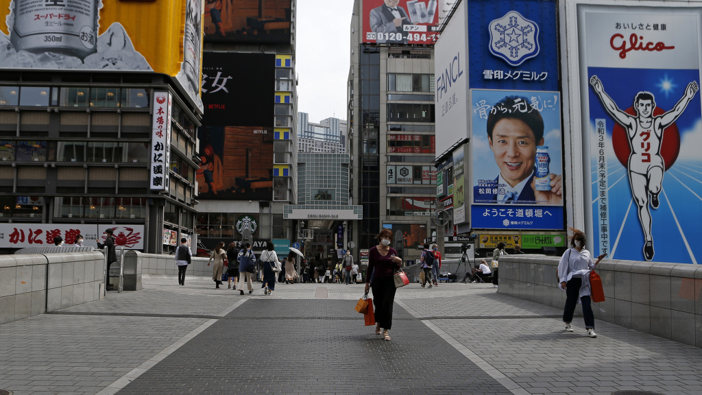Japan on Friday announced a third state of emergency over the COVID-19 pandemic with new restrictions taking effect Sunday. Here, a woman walks on a quiet Dotonbori Street. The arcade is normally one of Osaka's most popular tourist areas.