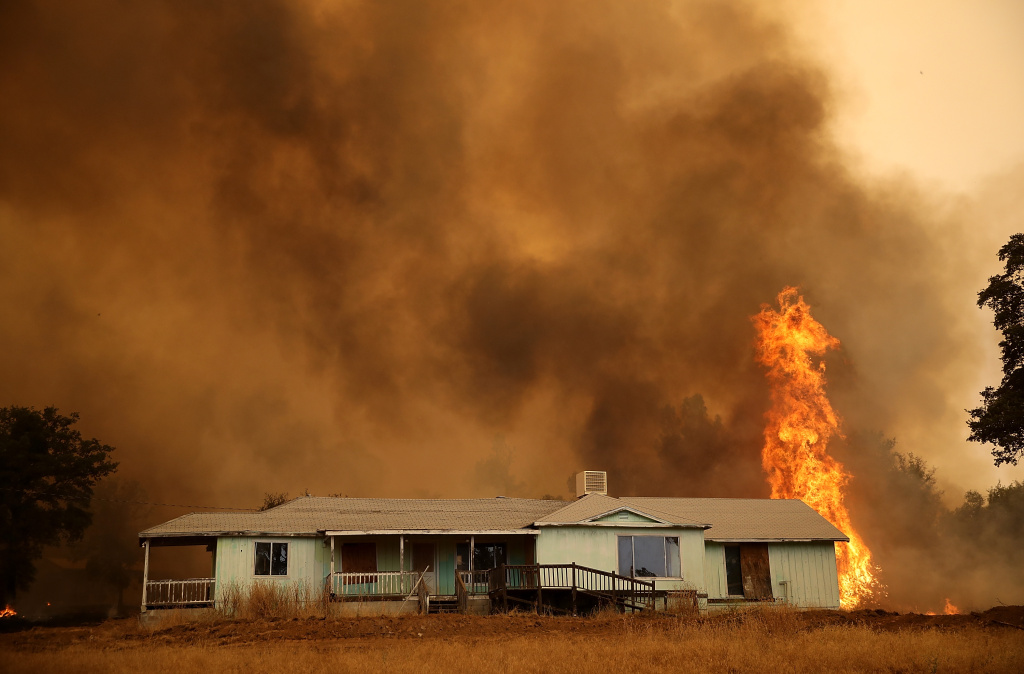 Flames approach a home as the Detwiler Fire burns through brush on July 19, 2017 in Mariposa, California.