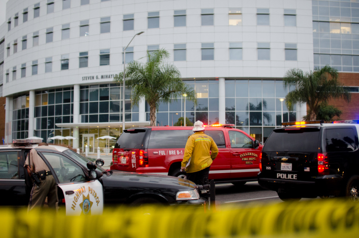 Police plan their strategy to search Mihaylo Hall at Cal State Fullerton in Fullerton, Calif., Wednesday, Dec. 12, 2012. One of five robbery suspects, believed to be armed, has barracaded himself inside the building.