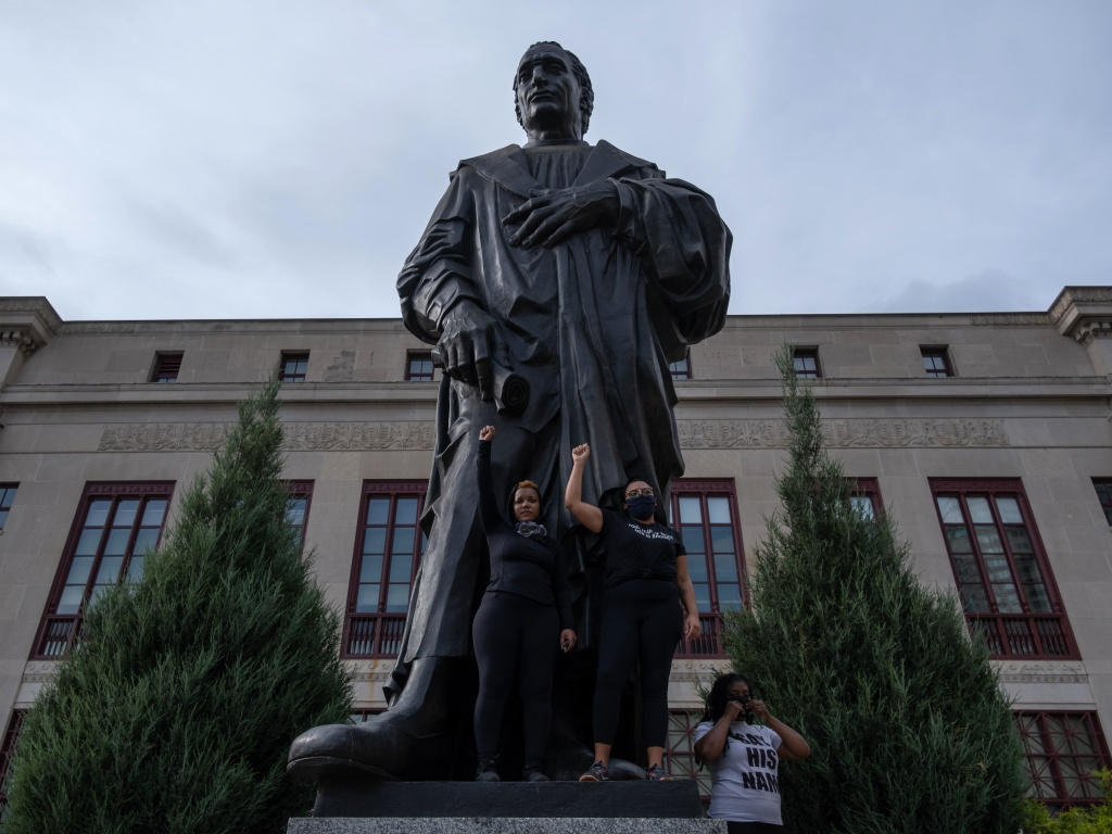 Demonstrators stand on the base of a Christopher Columbus statue in front of City Hall during a protest against police brutality Saturday in downtown Columbus, Ohio.