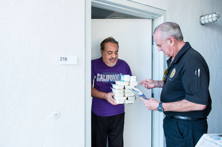 Volunteer Mike Kearin delivers food to client Jesus Barron in November 2016.