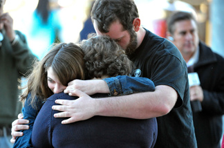 Gia, center, Georgia, left, and John Cobb, of Tucson, embrace outside the office of Congresswoman Gabrielle Giffords after Giffords was shot Saturday, Jan. 8, 2011, at a grocery store in Tucson, Ariz.