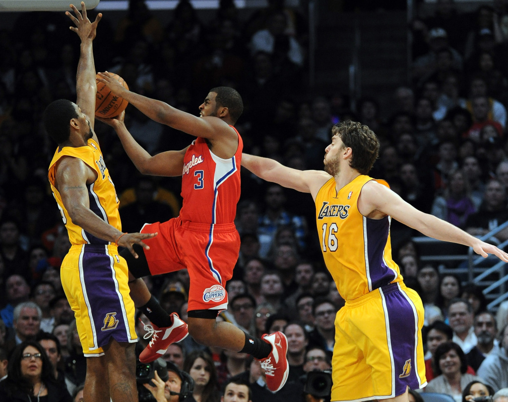 Chris Paul #3 of the Los Angeles Clippers drives to the basket on Metta World Peace #15 and Pau Gasol #16 of the Los Angeles Lakers at Staples Center. The Los Angeles Clippers were swept out of the playoffs, ending a season to remember and build on for the much-maligned franchise.