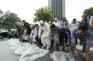 People pray before radical Muslim cleric Pierre Vogel, who spoke to a gathering of sympathizers.