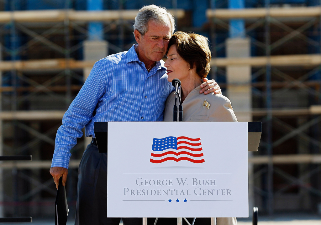 Former President George W. Bush hugs his wife, Laura Bush, during the George W. Bush Presidential Center Topping Out Ceremony on October 3, 2011 in Dallas, Texas.