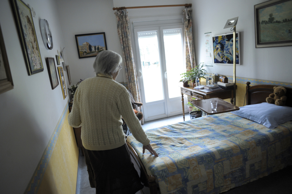 A woman, suffering from Alzheimer's disease, walks in her room in a retirement house in Angervilliers, eastern France.
