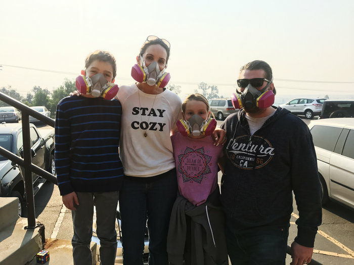 Nancy and Jay Blomquist stand outside the Local Assistance Center in Ventura, Calif. with their twins Alexander and Olivia. The family wears masks to protect themselves from the ash and smoke in the air from thee Thomas fire.