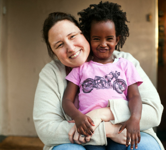 Trista Schroeder and her daughter, Luli, 3, sit outside their home on Monday afternoon. Schroeder adopted Luli at birth in Ethiopia.
