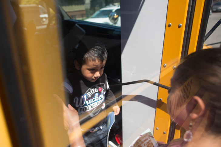 A mother picks up her child from the bus that takes children home around Oxnard from a day at Headstart.