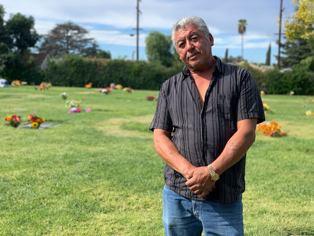 Julio Osorio stands in the Valhalla Memorial Park Cemetery near his mother's grave. (Emily Elena Dugdale/KPCC)