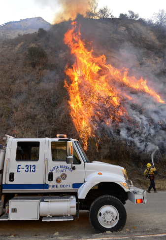Parked on the closed U.S. Highway 101, a Santa Barbara County Fire Department fire engine and crew douse a hot spot while working the Solimar Beach wildfire in Ventura County on Dec. 26, 2015. The fire, which began on Christmas night, has charred more than 1,250 acres.