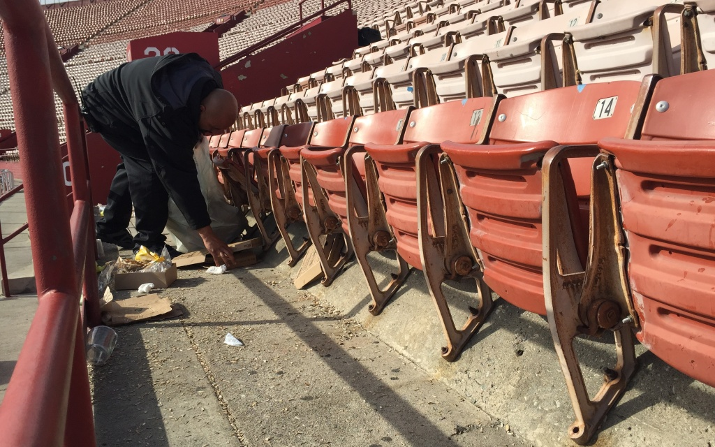 Francis Gonzalez cleans up trash at the LA Memorial Coliseum, which has reached a milestone: zero waste after football games. Gonzalez is a project supervisor with ABM.