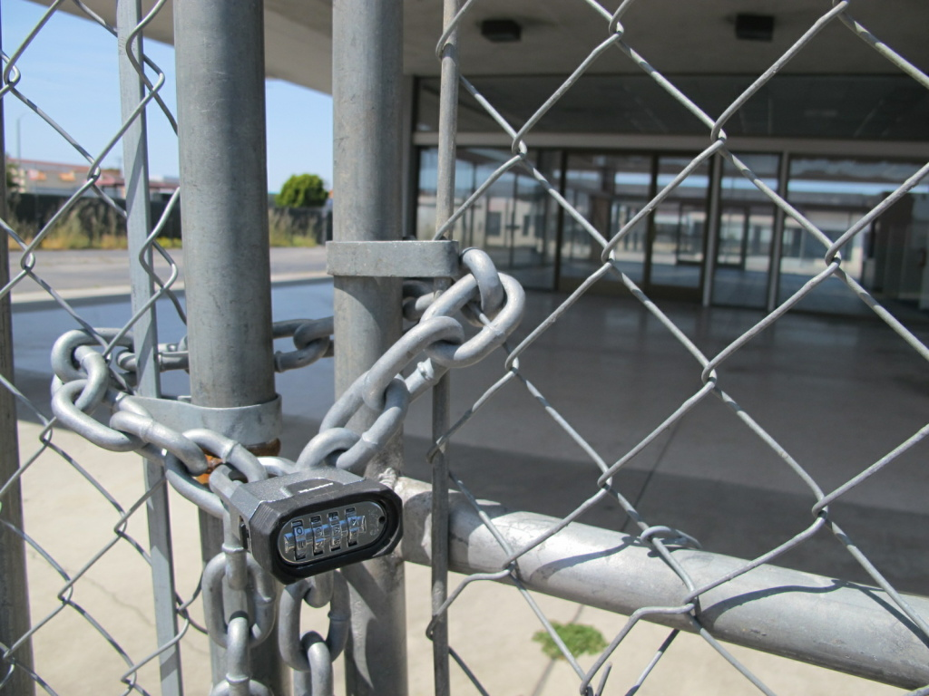 A lock keeps a gate closed at a vacant car dealership on Hawthorne Boulevard in Torrance.