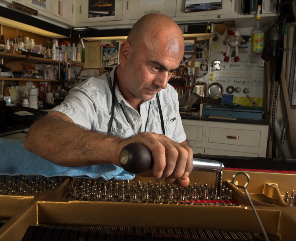 Steve Bagmanyan, a piano repair technician tunes a Steinway and Sons piano at the LAUSD Music Repair Shop.