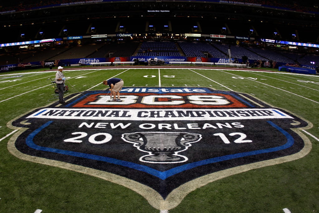 Grounds crew workers paint the Allstate BCS Championship logo on the field at the Mercedes-Benz Superdome on January 8, 2012 in New Orleans, Louisiana.