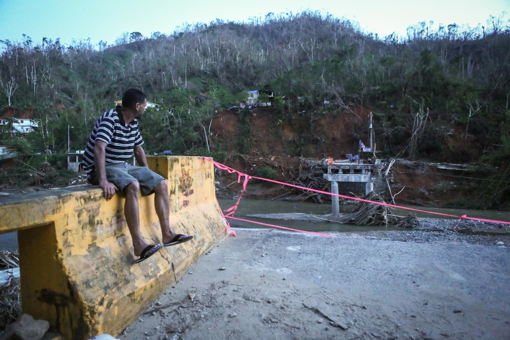A man sits on the edge of a broken bridge spanning the Vivi River on October 20, 2017 in Utuado, Puerto Rico. The bridge was washed away during Hurricane Maria.