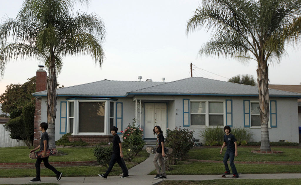 Unidentified teens walk past the home of the family of Arifeen David Gojali in Pomona, Calif., on Tuesday, Nov. 20, 2012. Three California men excited at the prospect of training in Afghanistan to become terrorists prepared, authorities say, by simulating combat with paint ball rifles, wiping their Facebook profiles of any Islamic references and concocting cover stories. Family members told The Associated Press they were shocked by Gojali's arrest, but added that the unemployed Gojali had drifted away from the family in the recent months.