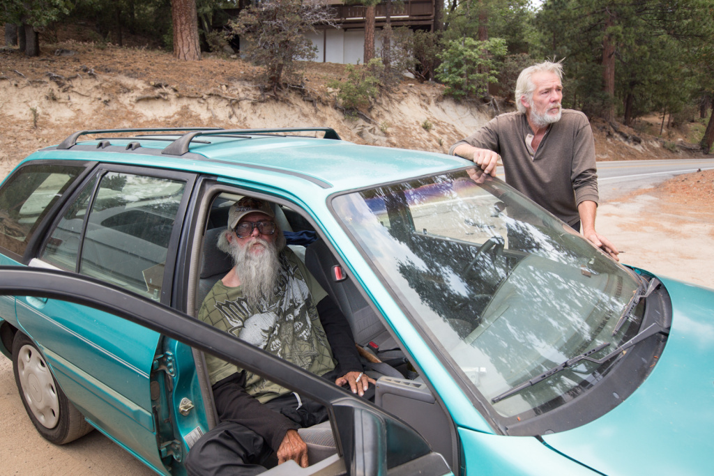 Wayne Trott and David Atwood wait by their car after being evacuated from Idyllwild, Calif. due to the Mountain Fire.