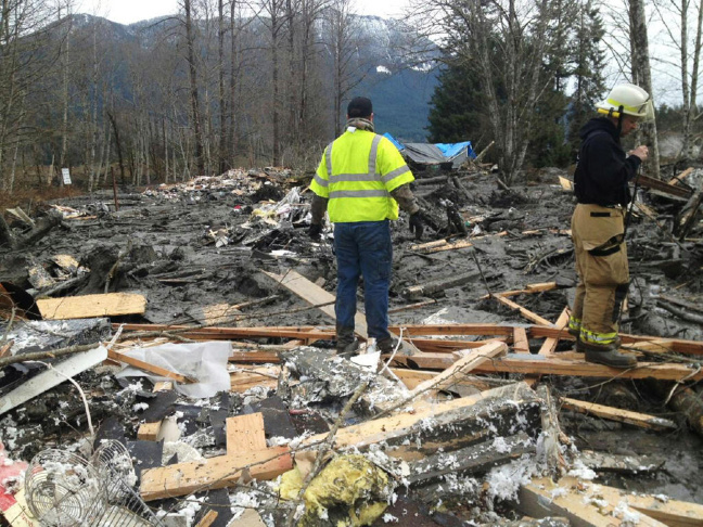 In this handout from the Washington State Patrol, emergency workers examine debris after a mudslide March 22, 2014 in Snohomish County, Washington. According to reports, 18 people are still missing after a mudslide killed three and injured another eight. The mudslide is said to measure a square mile and 15 feet deep in places.