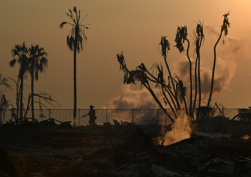 A firefighter hoses down flareups at the two story Hawaiian Village Apartment complex that burnt to the ground during the Thomas wildfire in Ventura, California on December 5, 2017. Firefighters battled a wind-whipped brush fire in southern California that has left at least one person dead, destroyed more than 150 homes and businesses and forced tens of thousands to flee. / AFP PHOTO / MARK RALSTON        (Photo credit should read MARK RALSTON/AFP/Getty Images)