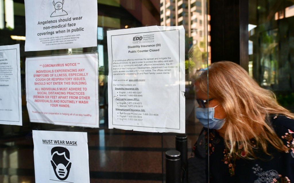 A woman wearing a facemask enters a building where the Employment Development Department has its offices in Los Angeles.