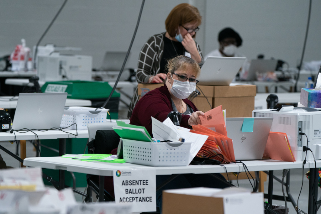 Election personnel sort ballots in preparation for an audit at the Gwinnett County Board of Voter Registrations and Elections offices on Saturday in Lawrenceville, Ga. President Trump's attempt at legal action to contest the results of the election have so far been mostly unsuccessful.