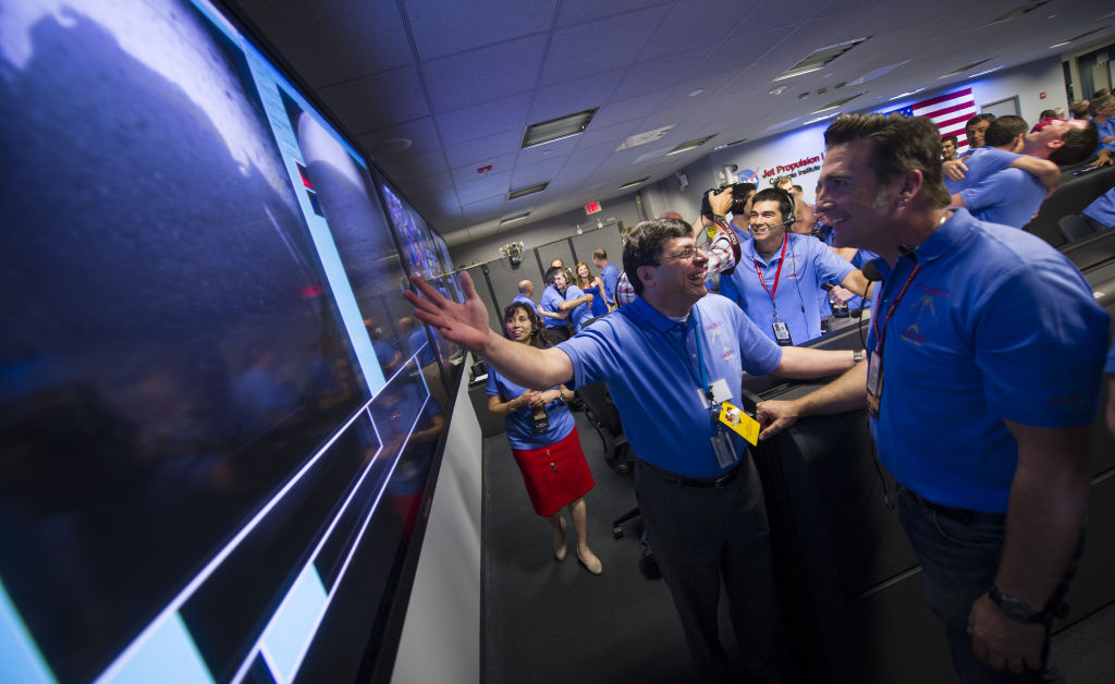 Christopher J. Scolese, Director of NASA's Goddard Space Flight Center, left, congratulates, MSL Entry, Descent and Landing Engineer Adam Steltzner as they look at the first images of Mars to come from the Curiosity rover, shortly after it landed on Mars.