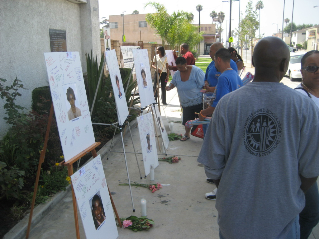 Visitors and passersby write messages on photos of Grim Sleeper victims on display at Bethel AME Church in South Los Angeles