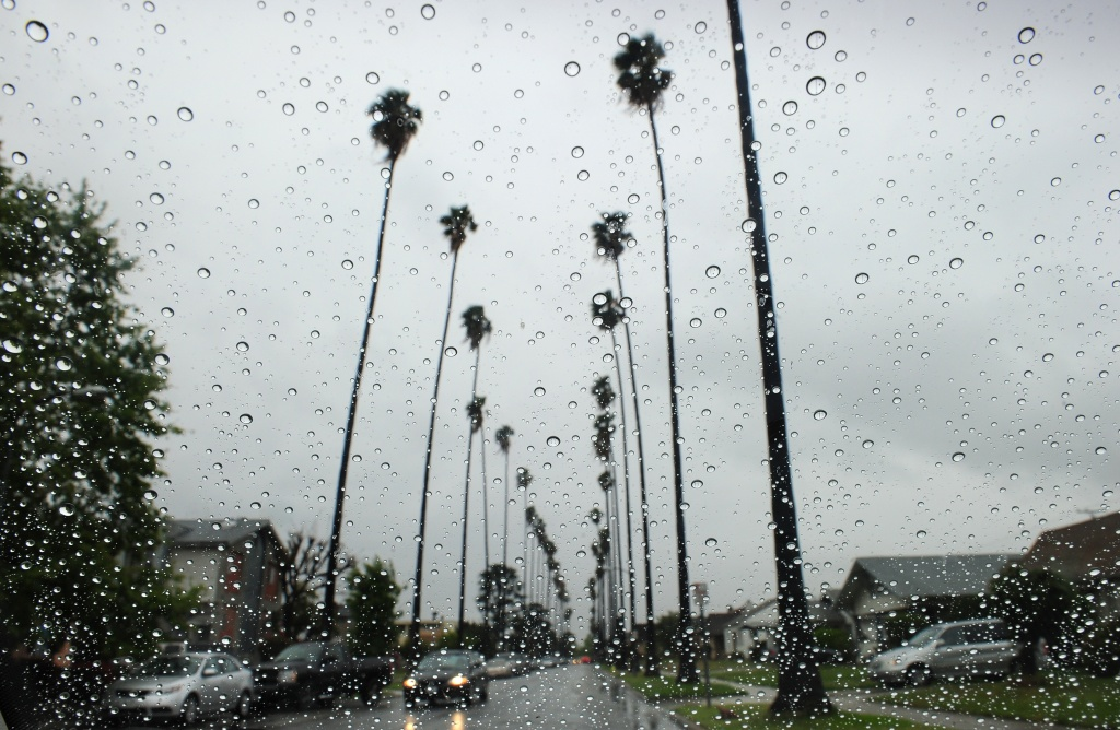 In this file photo, raindrops are seen on a vehicle's windshield as a car makes its way down a tree-lined street in Alhambra.
